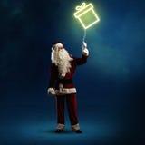 Santa Claus está guardando um presente de brilho Fotografia de Stock Royalty Free