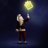 Santa Claus está guardando um presente de brilho Foto de Stock