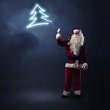 Santa Claus está guardando uma árvore de Natal de brilho Foto de Stock