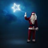 Santa Claus está guardando uma estrela de brilho Imagem de Stock Royalty Free