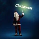 Santa Claus está guardando uma palavra de brilho do Natal Fotos de Stock