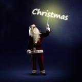 Santa Claus está guardando uma palavra de brilho do Natal Imagens de Stock