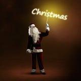 Santa Claus está guardando uma palavra de brilho do Natal Foto de Stock