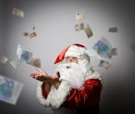 Santa Claus está soplando euro Imagen de archivo libre de regalías