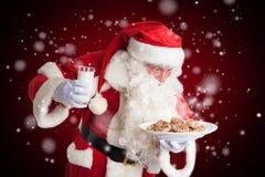 Santa Claus est heureuse au sujet du lait et des biscuits image libre de droits