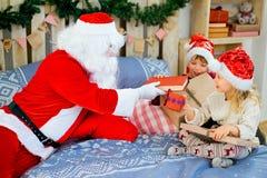 Santa Claus et deux enfants s'asseyant sur le lit Photographie stock libre de droits
