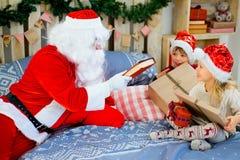 Santa Claus et deux enfants s'asseyant sur le lit Image libre de droits
