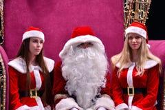 Santa Claus et deux Santa helpersnear l'arbre dans le lobby du centre commercial de galaxie photos stock