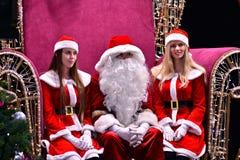 Santa Claus et deux Santa helpersnear l'arbre dans le lobby du centre commercial de galaxie image libre de droits