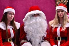 Santa Claus et deux Santa helpersnear l'arbre dans le lobby du centre commercial de galaxie photo stock