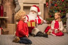 Santa Claus et enfants avec des cadeaux de Noël Image libre de droits