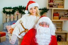 Santa Claus et fille mignonne étant prêtes pour Noël Photos libres de droits