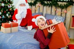 Santa Claus et garçon mignon étant prêts pour Noël Image stock