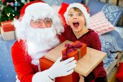 Santa Claus et garçon mignon étant prêts pour Noël Photographie stock