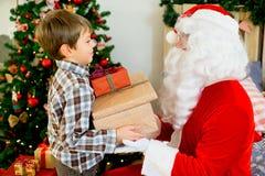 Santa Claus et garçon mignon étant prêts pour Noël Photos stock