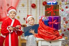 Santa Claus et l'assistant dressent une liste de cadeaux et les trouvent Photos libres de droits