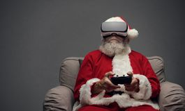 Santa Claus experiencing virtual reality. At home and playing videogames using a controller, he is wearing a VR headset Stock Image