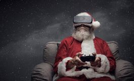 Santa Claus experiencing virtual reality. At home and playing videogames using a controller, he is wearing a VR headset and he is surrounded by snow Royalty Free Stock Images