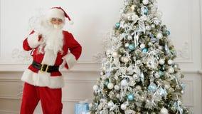 Santa Claus faisant la danse drôle de robot à côté de l'arbre de Noël Images stock