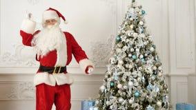 Santa Claus faisant la danse moderne à côté de l'arbre de Noël Photo libre de droits