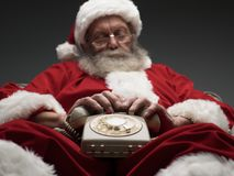 Santa Claus falling asleep while waiting for a phone call. He is relaxing on the armchair and holding a vintage phone on his lap stock image