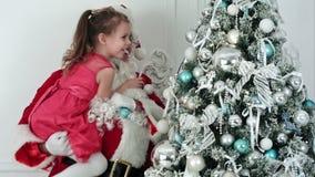 Santa Claus falsa que adorna un árbol de navidad que detiene a una niña en su brazo almacen de video