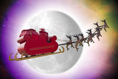 Santa Claus Fantasy. Santa Claus riding a sleigh in dusk led by reindeers passing in front of the moon Stock Photo