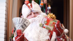 Santa claus, father christmas, father frost chooses what is better to give money dollars or a Christmas gift in a. Colorful paper wrapper with a gold bow as a stock footage