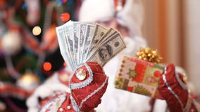 Santa claus, father christmas, father frost chooses what is better to give money dollars or a Christmas gift in a. Colorful paper wrapper with a gold bow as a stock video footage