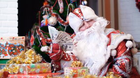 Santa claus, father christmas, father frost is fanning himself with a fan of dollars, he sits at a table, among the. Christmas gifts, in the background is a stock video footage