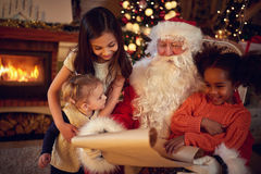 Santa Claus father reading wish list with mixed race little girl Stock Photos