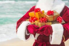 Santa Claus fecha-se acima com muitos presentes dourados na praia do mar Imagens de Stock
