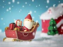 Santa Claus felice con il contenitore di regali sulla slitta della neve che va nevicare casa vicino alla casa della neve abbia il fotografia stock libera da diritti
