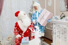 Santa Claus felice e la bella nipote stanno sedendo all'interno nell'interno del ` s del nuovo anno e stanno tenendo il ` s del n Fotografie Stock