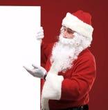 Santa Claus feliz que olha para fora atrás do sinal vazio Imagens de Stock Royalty Free