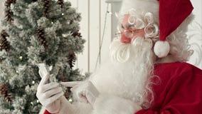 Santa Claus feliz que verifica acima dos email do Natal das crianças em seu telefone video estoque