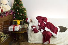 Santa Claus is asleep on the couch. Santa Claus fell asleep on a white sofa in the room with a Christmas tree Stock Photo