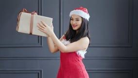 Santa Claus femenina asiática sonriente que celebra la caja de regalo grande del cartón con el arco en el estudio en fondo gris