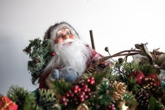 Santa. Claus figure wearing glasses amongst the Christmas decorations. Shallow focus Stock Photo