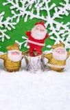 Santa Claus figures. Three cute santa clauses figure on the snow Royalty Free Stock Photo
