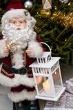Santa Claus figurine with candle holder at Xmas tree Stock Photos