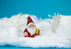 Santa Claus figurine. With gift on blue background Stock Photo