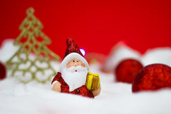 Santa Claus figurine. With gift on red background Stock Photo