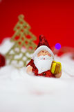 Santa Claus figurine. With gift on red background Stock Photos