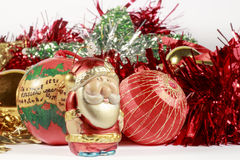 Santa Claus figurine, red garland, baubles and other Christmas decorations Royalty Free Stock Images