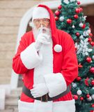 Santa Claus With Finger On Lips Against Christmas Stock Photos