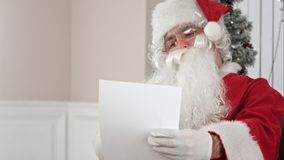 Santa Claus finishing writing and checking his letter to a kid. Professional shot on BMCC RAW with high dynamic range. You can use it e.g. in your commercial Royalty Free Stock Photo