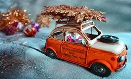 Santa Claus flees with an orange car, on the snow, with Christmas decorations