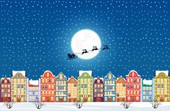 Santa Claus flies over a decorated snowy old city town at Christmas eve. Royalty Free Stock Images