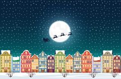 Santa Claus flies over a decorated snowy old city town near moon at Christmas eve. Royalty Free Stock Images